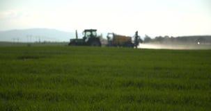 Lo spruzzo del trattore fertilizza sul campo con i prodotti chimici nel campo dell'agricoltura video d archivio