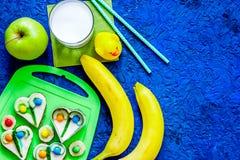 Lo spuntino di Fuit per clildren Panini divertenti, frutti e latte sul copyspace blu di vista superiore del fondo della tavola Immagini Stock Libere da Diritti