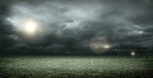 Lo stadio di calcio immaginario con le nuvole e la pioggia scure, rappresentazione 3d Fotografia Stock