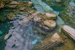 Lo stagno antico di Cleopatra con acqua e le colonne del turchese in Pamukkale fotografia stock
