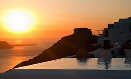 Lo stagno, la siluetta della roccia di Skaros e la vista della caldera di tramonto a Santorini Fotografia Stock
