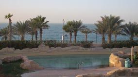Lo stagno vuoto in un hotel nell'iarda con le palme tropicali, mare aperto è nel fondo, area di località di soggiorno stock footage
