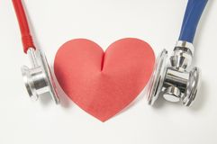 Lo stetoscopio due blu e rosso è lato destro e sinistro esaminato di forma del cuore dell'auscultazione o di ascolto su fondo bia fotografia stock