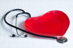 Lo stetoscopio e un piatto rosso del cuore sono a dieta il concetto Fotografie Stock