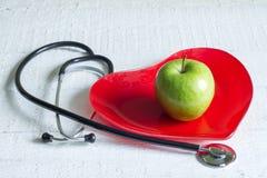Lo stetoscopio e un piatto rosso del cuore sono a dieta il concetto Immagini Stock