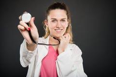 Lo stetoscopio femminile attraente della tenuta di medico gradisce consultarsi Fotografie Stock Libere da Diritti