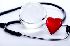 Lo stetoscopio, il globo ed il cuore modellano su bianco Fotografie Stock Libere da Diritti