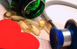 Lo stetoscopio, il grafico dell'elettrocardiogramma, le compresse ed il cuore modellano Fotografia Stock