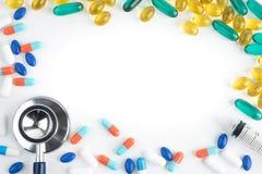 Lo stetoscopio, la siringa, le capsule dell'olio di pesce e le pillole sulla b bianca immagini stock