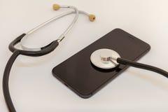 Lo stetoscopio sta pendendo contro lo schermo di uno smartphone nero fotografia stock libera da diritti