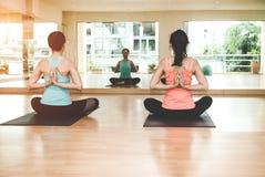 Lo stile di vita della gente dell'Asia che pratica e che si esercita vitale medita l'yoga nella stanza di classe Fotografie Stock Libere da Diritti