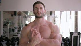 Lo stile di vita sano, forte tipo del culturista fa il riscaldamento dopo il muscolo in costruzione di allenamento di forza nel c stock footage