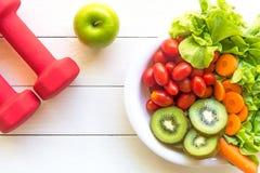 Lo stile di vita sano per le donne è a dieta con l'attrezzatura di sport, la verdura e la frutta fresche, mele verdi su di legno fotografia stock