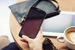 Lo stile di vita urbano moderno, il saltatore del caffè, fine su del ` s delle donne passa lo Smart Phone della tenuta Immagini Stock Libere da Diritti