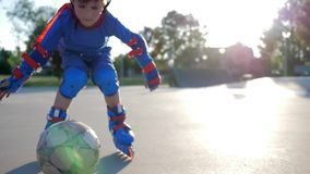 Lo stile libero, bambino attivo in ginocchiere gioca sui rulli al campo da giuoco dei bambini su aria aperta