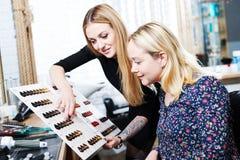 Lo stilista aiuta il cliente femminile a scegliere il colore della tintura per capelli con il grafico dei campioni dei capelli immagini stock libere da diritti