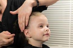 Lo stilista di capelli produce alla ragazza un panino dell'acconciatura immagini stock libere da diritti