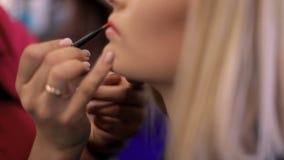 Lo stilista dipinge le labbra ad una ragazza in salone, primo piano video d archivio