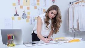 Lo stilista disegna gli schizzi per una nuova collezione ed esamina il computer archivi video