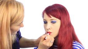 lo stilista disegna il contorno delle labbra di modello del ` s con una matita rossa il truccatore applica il rossetto con la spa archivi video