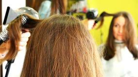 Lo stilista esegue i riccioli per la donna riccio-dai capelli castana stock footage