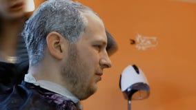 Lo stilista femminile tinge i capelli dell'uomo maschio in parrucchiere, nella cura personale e nella bellezza video d archivio