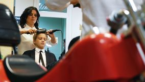 Lo stilista pettina ed asciugacapelli i capelli del ` s del ragazzino archivi video