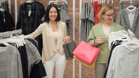 Lo stilista seleziona un insieme dell'abbigliamento casual alle donne in un deposito al centro commerciale video d archivio