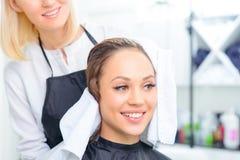 Lo stilista sta asciugandosi fuori dai capelli dei clienti Fotografie Stock