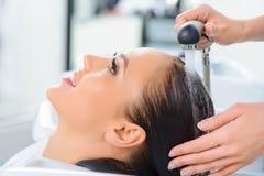 Lo stilista sta lavando i capelli dei clienti Immagine Stock Libera da Diritti
