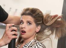 Lo stilista usa la lacca sulla donna sorpresa fotografia stock libera da diritti
