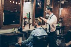 Lo stilista vestito di classe del negozio di barbiere sta lavorando per i capelli perfetti fotografia stock libera da diritti