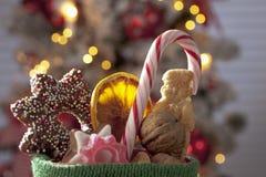 Lo stivale di Santa Claus in pieno con le golosità di natale si chiude sull'albero di Natale nel fondo Fotografie Stock Libere da Diritti