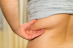Lo stomaco della donna del primo piano dall'angolo di profilo, afferrante sull'eccessivo grasso laterale facendo uso delle dita,  immagini stock