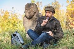 Lo storico istruito si siede prima della scultura di pietra sul monticello Fotografia Stock