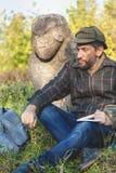 Lo storico istruito si siede prima della scultura di pietra sul monticello Fotografia Stock Libera da Diritti