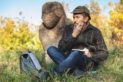 Lo storico istruito si siede prima della scultura di pietra sul monticello Immagine Stock