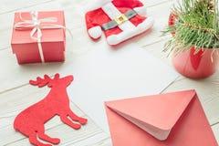 Lo strato del Libro Bianco con la busta, il contenitore di regalo di Natale, il costume del giocattolo di Santa, cervo gioca con  Fotografie Stock