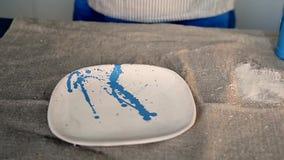 Lo stregone spruzza la pittura blu su un piatto bianco Sulla tavola con tela da imballaggio Workshop creativo archivi video