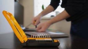 Lo stregone utilizza un cacciavite per torcere la vite sul coperchio del taccuino archivi video