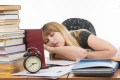 Lo studente è caduto addormentato al suo scrittorio che prepara per un esame Fotografie Stock