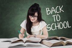 Lo studente abile di nuovo alla scuola scrive sui libri Fotografie Stock
