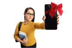 Lo studente adolescente femminile che mostra un telefono si è avvolto con il nastro rosso a Fotografie Stock