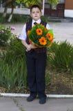 Lo studente adorabile della scuola costa con un mazzo dei fiori Fotografie Stock
