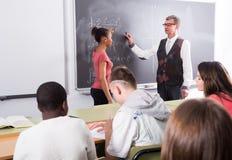 Lo studente afroamericano risponde vicino alla lavagna alla lezione di per la matematica Fotografia Stock