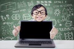 Lo studente allegro con il computer portatile mostra il gesto di mano Fotografia Stock