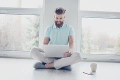 Lo studente allegro sta studiando con il suo computer portatile che si siede sul floo Fotografia Stock