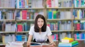 Lo studente asiatico di signora ha letto un libro nella biblioteca della città universitaria in Universit Fotografie Stock