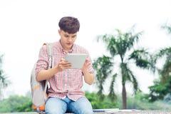 Lo studente asiatico maschio attraente sta utilizzando la città universitaria digitale in città universitaria Immagine Stock
