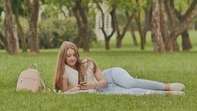 Lo studente attraente della ragazza con uno smartphone si trova su un parco dell'erba Resto durante lo studio archivi video